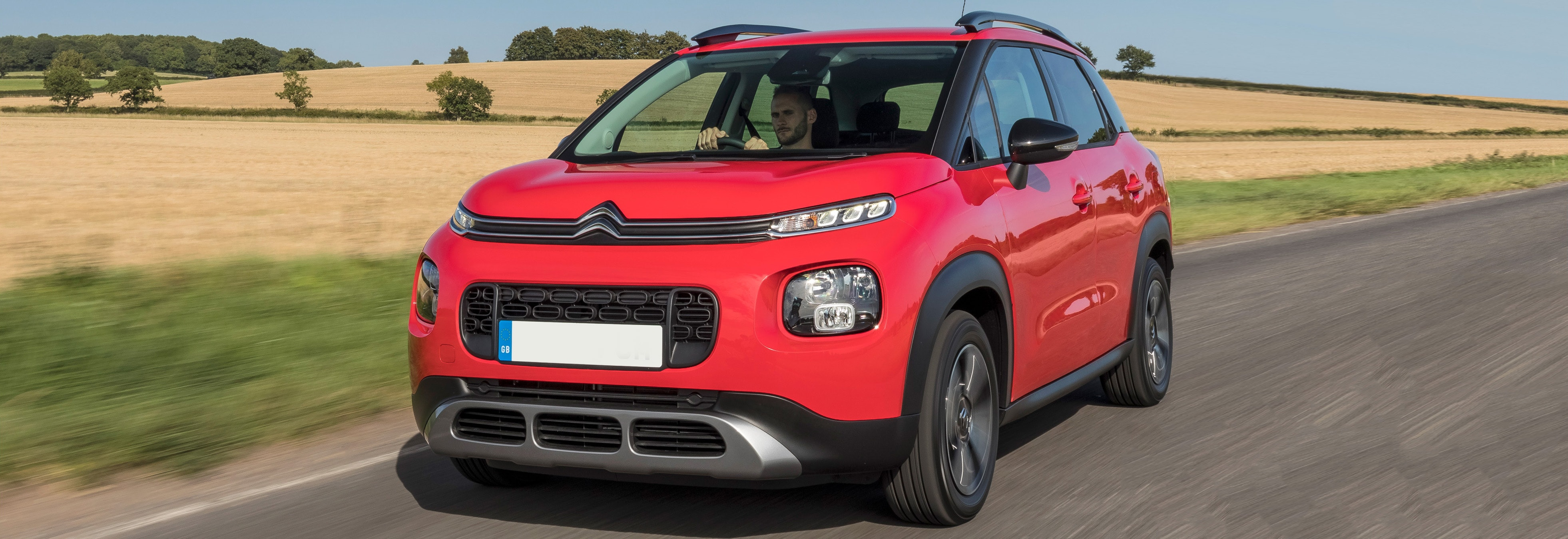 Red Citroen C3 Aircross driving, viewed from the front